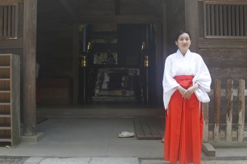 <p>A women stands next to the main shrine.</p>