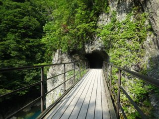 A bridge leads into a short tunnel on the trail through Dakigaeri Gorge