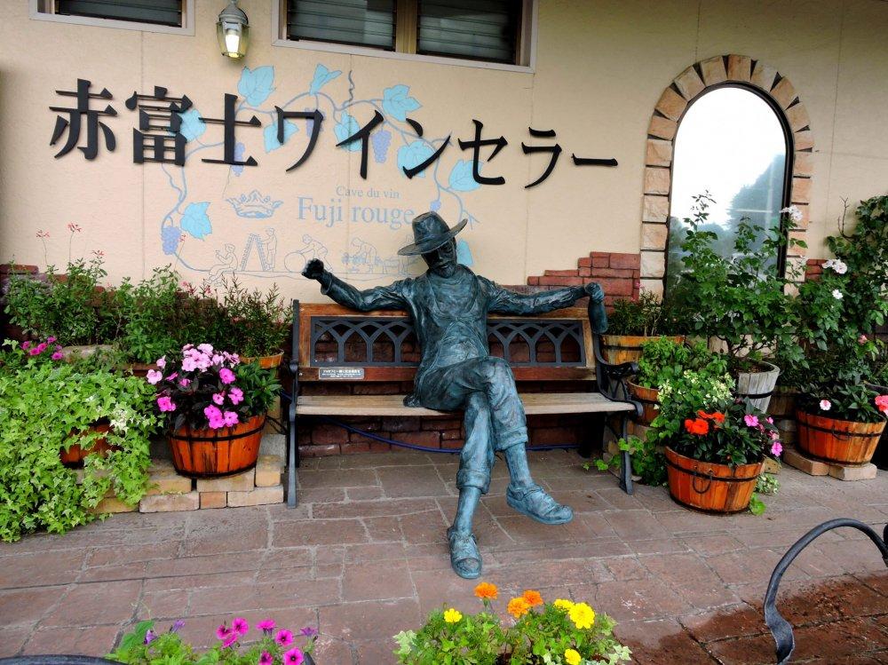 Вы можете попозировать с этой статуей на скамейке у входа