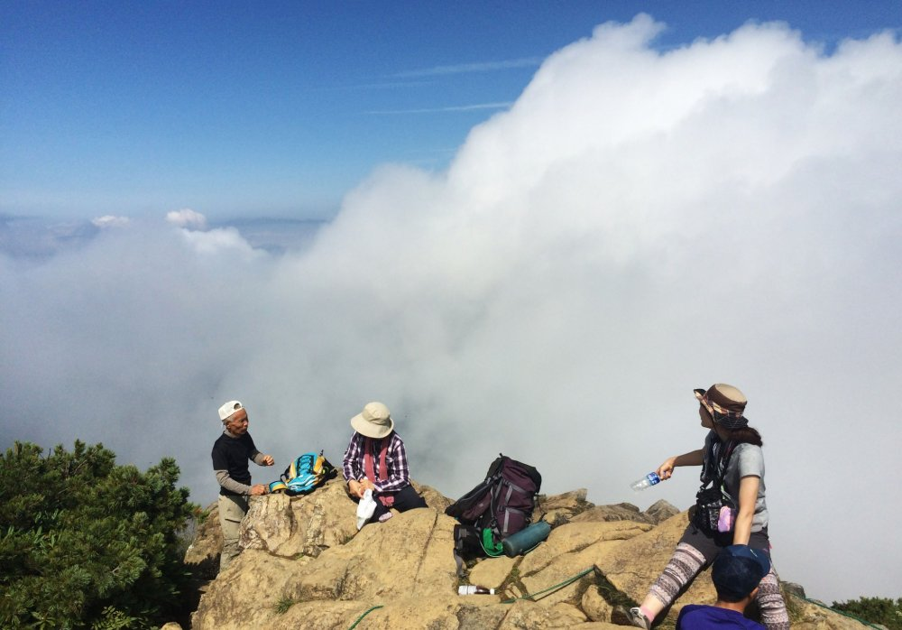 Hikers take a rest at the mountain top of Mt. Shibutsu.