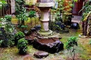 A lone stone lantern standing amidst a damp, mossy garden