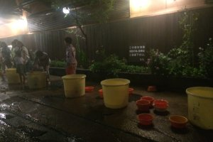 Buckets filled with hot spring water from hotels for guests and spectators to throw on the shrine.