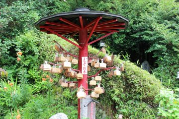 <p>Wooden emma tablets with wishes hanging from a wooden parasol</p>