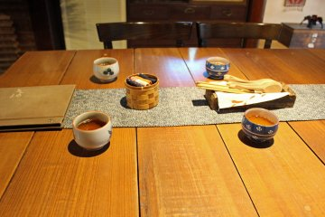 <p>Tea, oshibori cloths in their woven bamboo basket and other utensils</p>