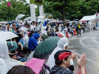 Hujan tak kunjung reda, namun penonton tetap antusias di bawah naungan payung