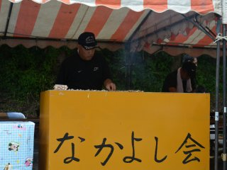 "A man at his food stall, the sign reads ""Let's Be Friends Association"""