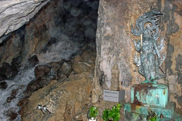 <p>The main chamber of the cave, the waterfall and a statue of Fudomyo, the Buddhist deity of discipline</p>