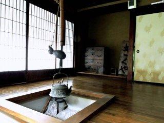 An iron kettle hanging over a sunken hearth in Kikuya Inn