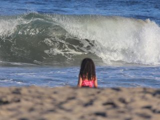 Little girl amazed by the waves