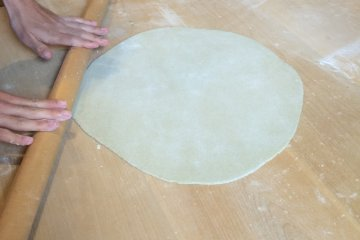<p>After first using our hands, we then used rolling pins to thin it out even thinner.</p>