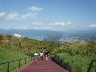 Jalur menanjak ini belum apa-apa karena masih ada yang lebih ekstrem. Terlihat Danau Toya dan Showa-shinzan di belakang!