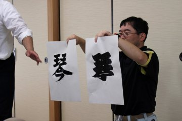 <p>The leader of the sumo calligraphy workshop demonstrates the difference between regular calligraphy (produced by holding the brush at a 90 degree angle) and sumo calligraphy (produced by using lots of ink and holding the brush at a 45 degree angle). The thick, heavy brush strokes of the sumo style calligraphy is indicative of a sumo&#39;s power and strength</p>