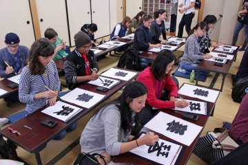 <p>Foreign and Japanese visitors to the museum try their hand at sumo calligraphy &nbsp;</p>