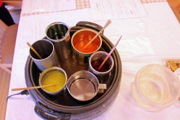 <p>Various liquid wax pots. The pot of clear wax at the bottom was used to finish and seal the candles made</p>
