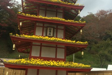 <p>Flowers on a replica of a famous Japanese building.</p>