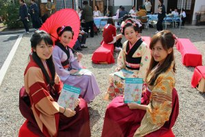 Kimono clad students from the Nara University of Medicine hold up the Jazzgle's event booklet