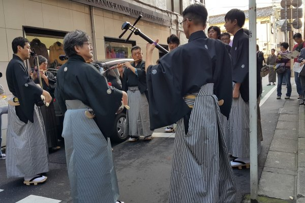 골목길 어귀에서 전통 음악을 연주하는 남자들.