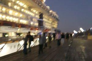 국제 여객선의 옥상, '고래의 등'에서 배를 바라보며 산책하는 사람들.