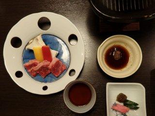 Para tamu yang memesan sayuran panggang dan irisan lembut daging sapi Jepang di sajikan pada  piring panas kecil mereka sendiri .