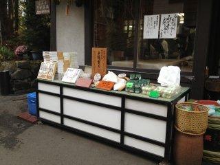Bahan pembuatan soba terjual di depan restoran. Jendela di belakangnya mempelihatkan ruangan pembuatan adonan soba.