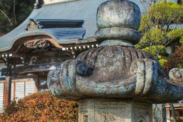 Каменный фонарь на фоне крыши главного здания