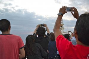 Passengers scramble to get a picture of the sunset