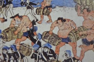 A contest of strength: Sumo wrestlers carry rice packs