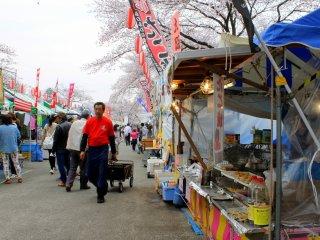 Jalanan dipenuhi barisan kios warna-warni yang menjual berbagai cemilan, mainan, dan minuman