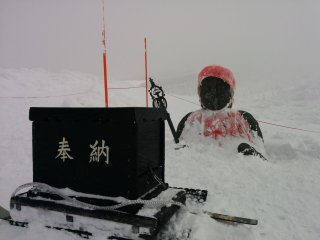 A Jizo statue buried up to its chest in the snowfall. Return during summer to see it in full