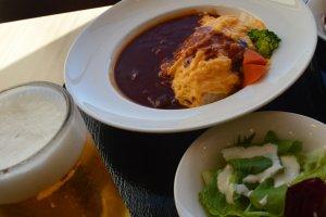 Satu set nasi kare, omelet, sayur dan salad serta segelas bir