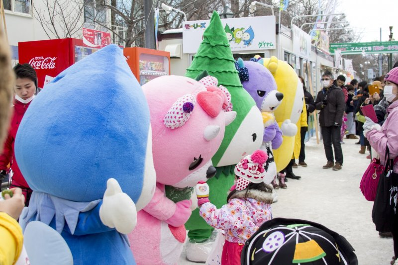 A little girl meets mascots at the festival