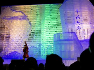 A singer performs against the illuminated backdrop of this enormous ice sculpture