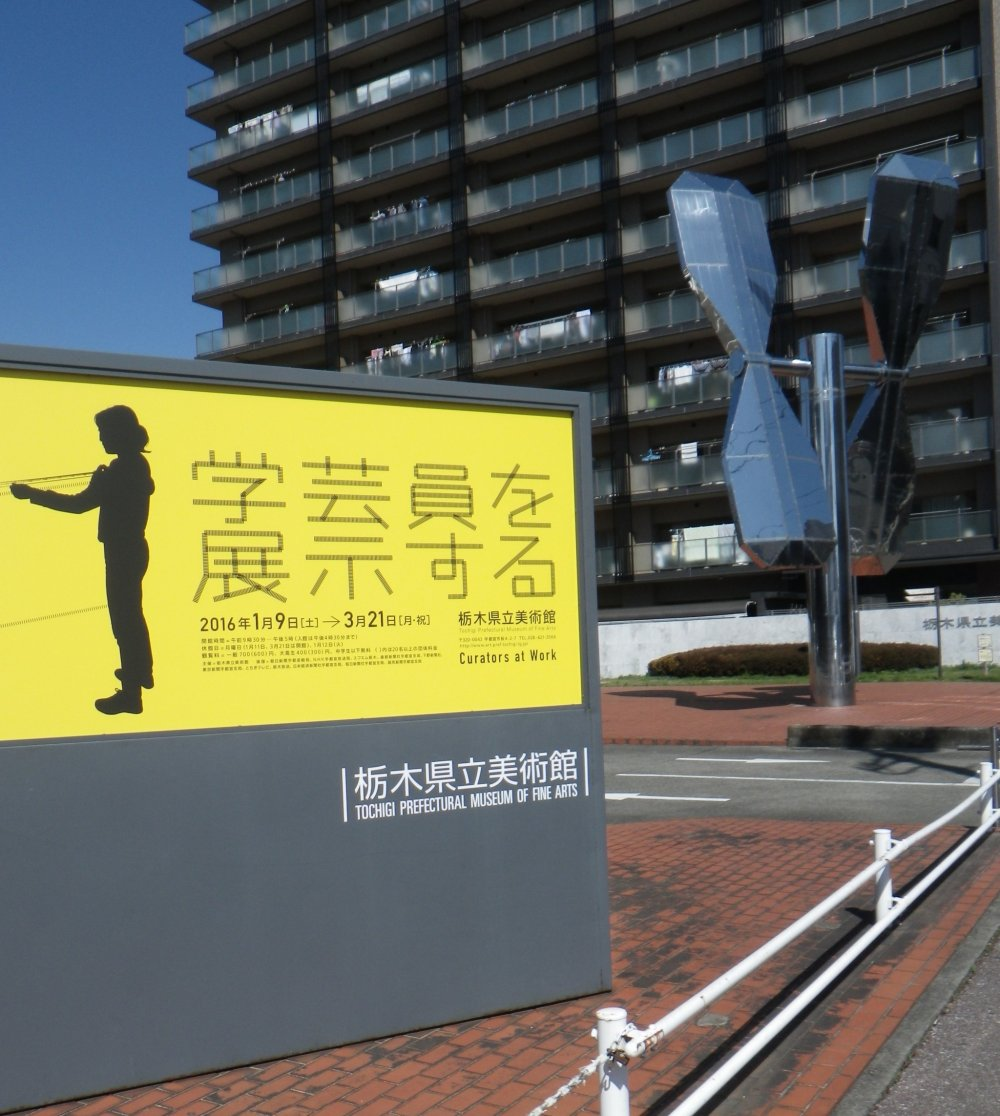 Each temporary exhibition lasts about two months. The poster for this one, Curators at Work, is black and yellow. Posters around town advertise the current exhibition. In the background, is a huge propeller installation which turns when it catches a breeze