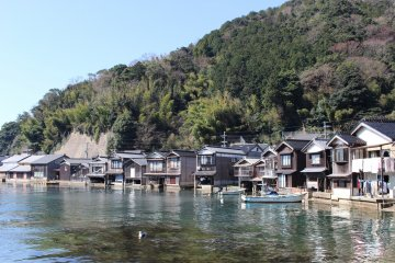 Boathouses line the shore at Ine Town