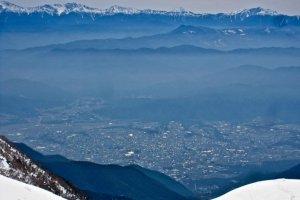 ภูเขาฟูจิ ยอดเขาคิทาดาเกะ ภูเขาที่สูงสุดอันดับ 1 กับ 2 ของญี่ปุ่นในภาพเดียวกัน ยอดเขาคิทาดาเกะเปนยอดเขาที่สองทางซ้ายของฟูจิ เมืองโคมางาเนะขยายข้ามหุบเขาที่ 2000 เมตรด้านล่าง (เมษายน)