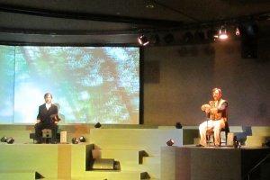 ภายใน auditorium ของพิพิธภัณฑ์ ตอนหุ่นกำลังแสดงการอภิปรายประเด็นปัญหาการเมืองของญี่ปุ่น