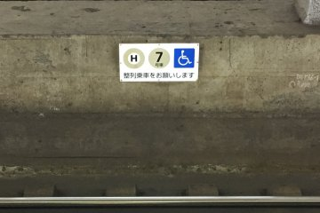 A sign on the Hibiya line tracks as seen from the platform, indicating that this approaching train car will feature priority wheelchair boarding/extra space