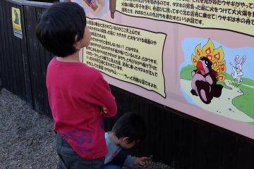哥哥很認真地閱讀著介紹カチカチ山的傳說站牌;弟弟也很認真地玩著地上的石子