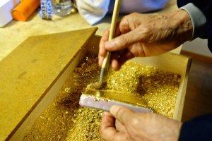 Nghệ nhân dán miếng vàng lá vào nắp hộp bằng cách quét lên một lớp bột vàng