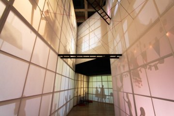 The installation of shadows reflecting on paper reaches up to the 3rd floor
