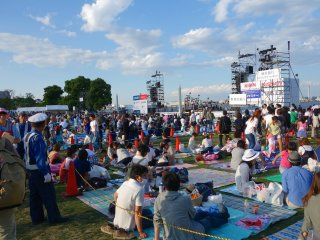 An open lawn area where people can sit and enjoy live performances on stage or grab an early spot before the fireworks show