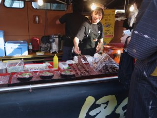 "A man in traditional yukata festival wear buys two meat skewers from the ""yakiniku"" lady"
