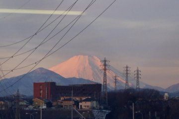 Mt. Fuji nestles in between power lines and buildings