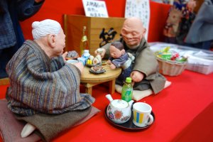 The puppets depict an intimate home scene between an elderly couple and their grandchild, presumably