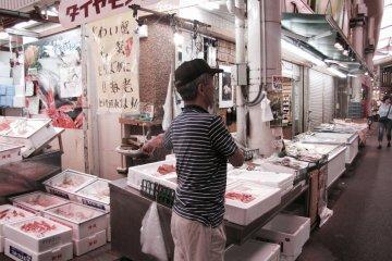 A vendor shows off his goods to passing trade