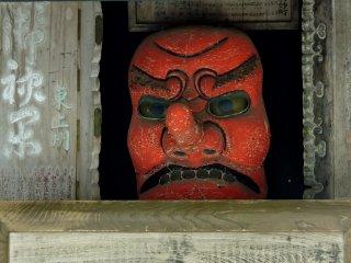 Uma cara de tengu olhando fixamente com os seus olhos amarelos