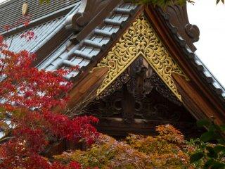 Массивная крыша храма в окружении красивой осенней листвы