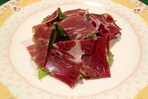 Green salad, covered in Iberico ham