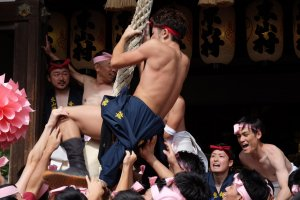 Each district tries to climb the rope at the Shinto temple
