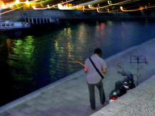 A musician tunes his guitar beside the river